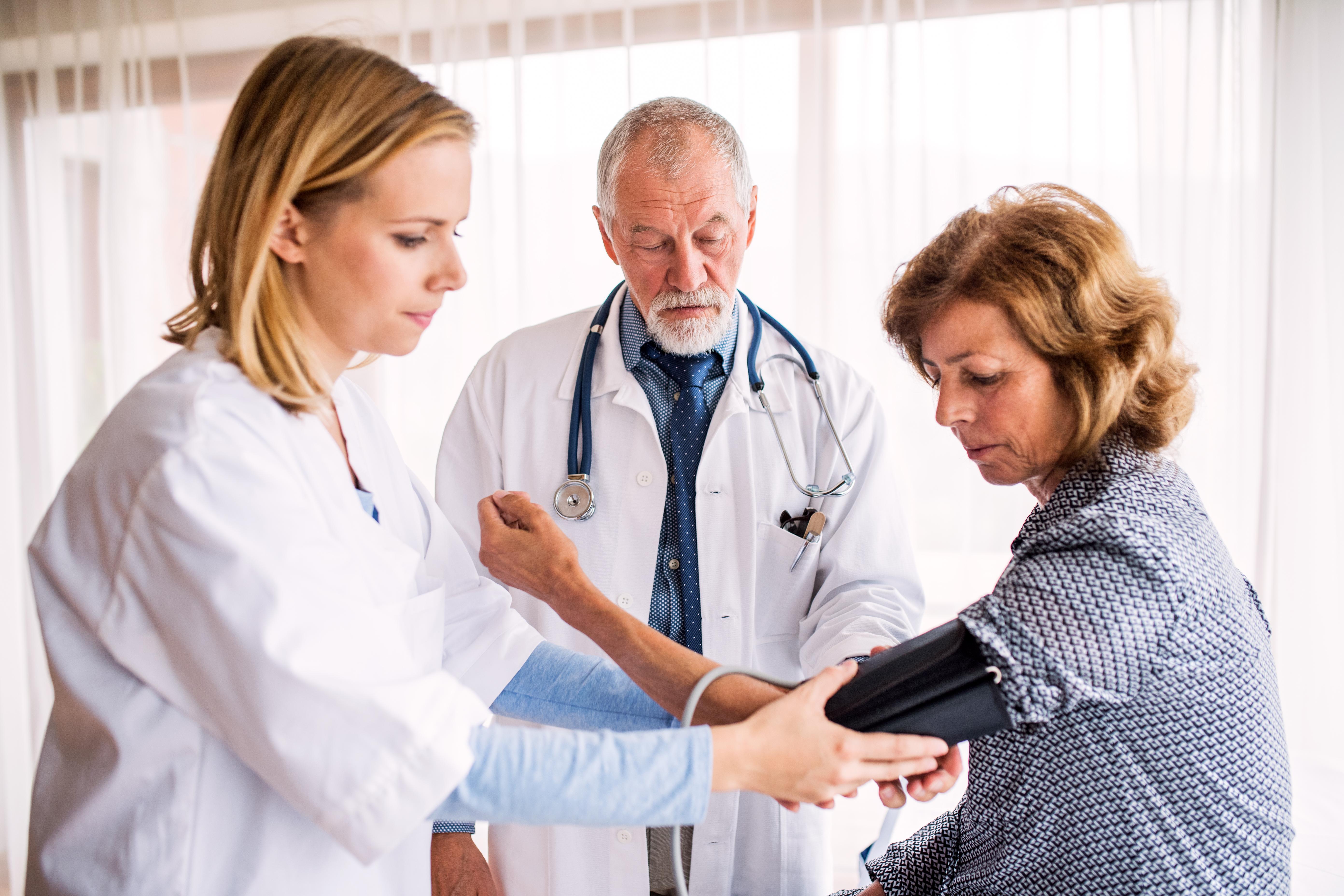 Senior doctor examining a senior woman. A nurse checking blood pressure of a senior woman.