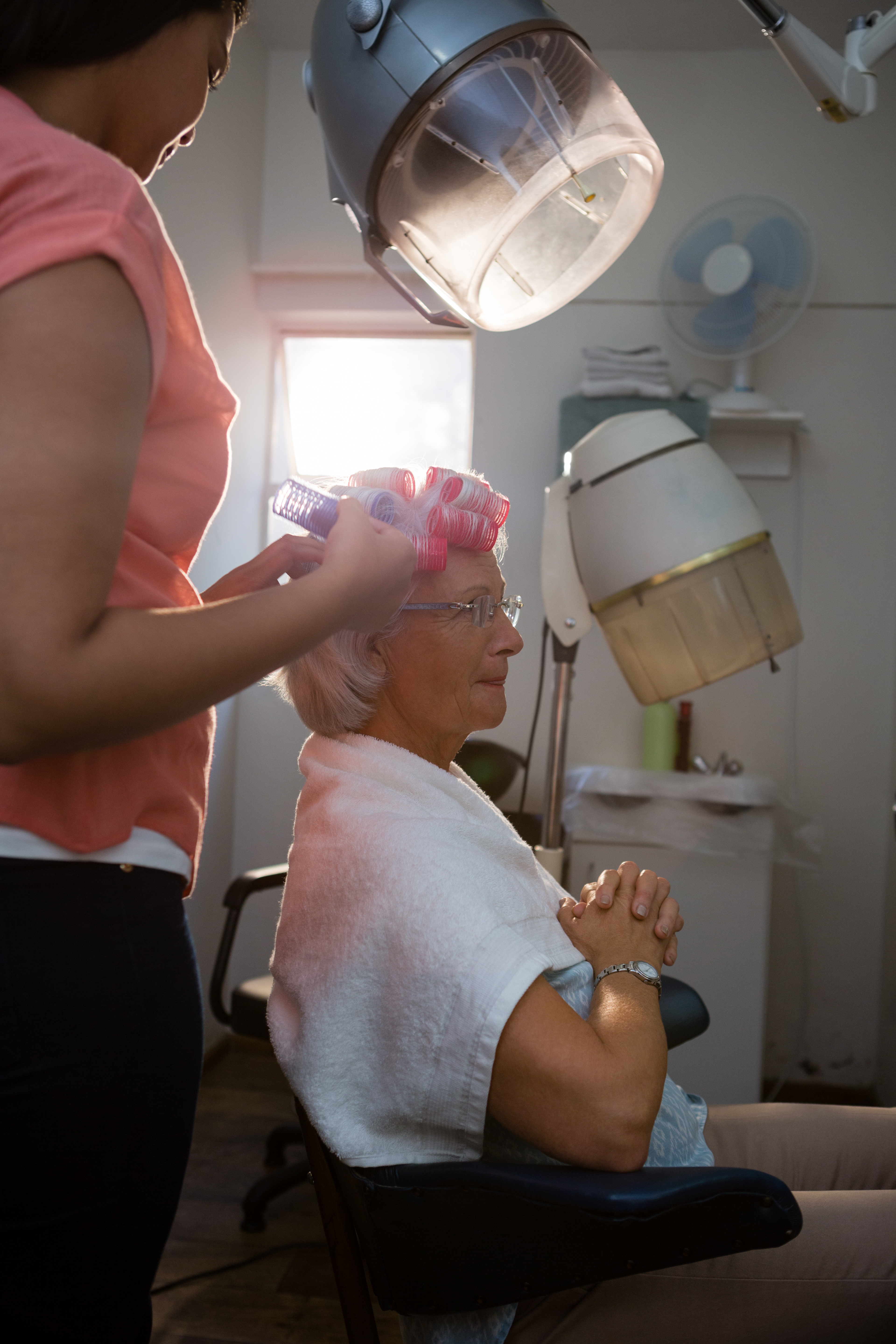Beautician removing curlers from senior woman hair at salon