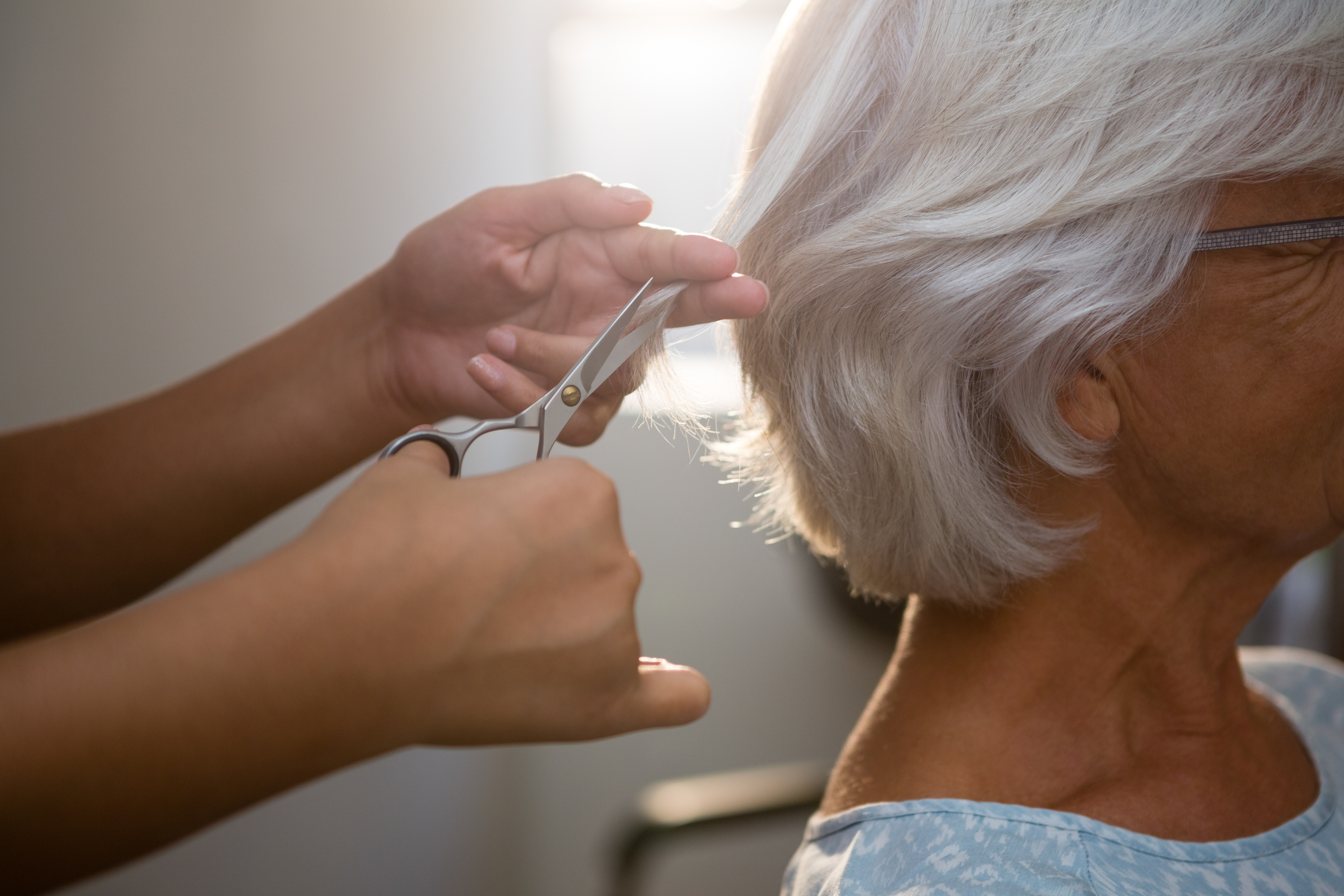 Cropped hands of beautician cutting hair of senior woman in salon