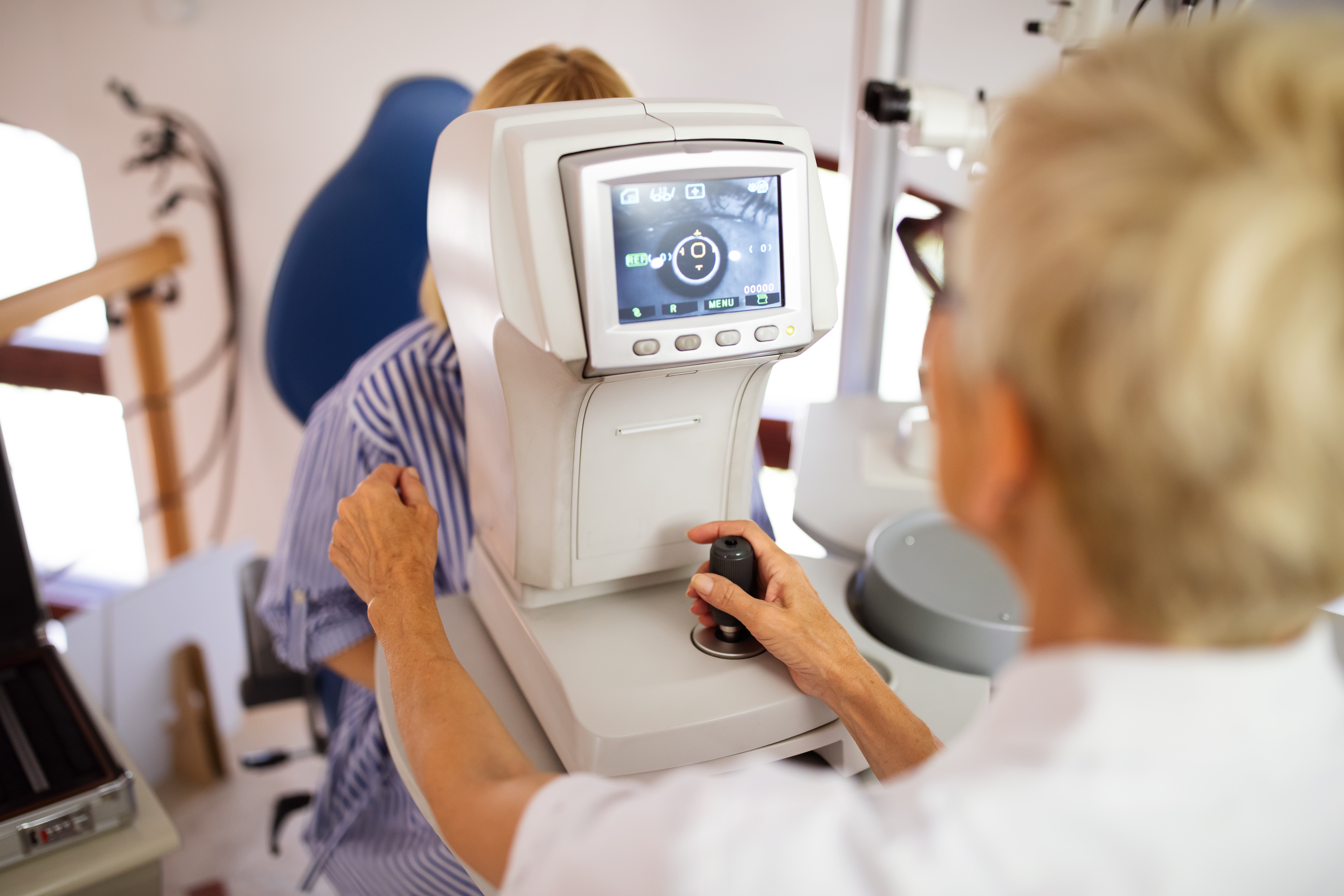 Senior optometrist examining patient in modern ophthalmology clinic