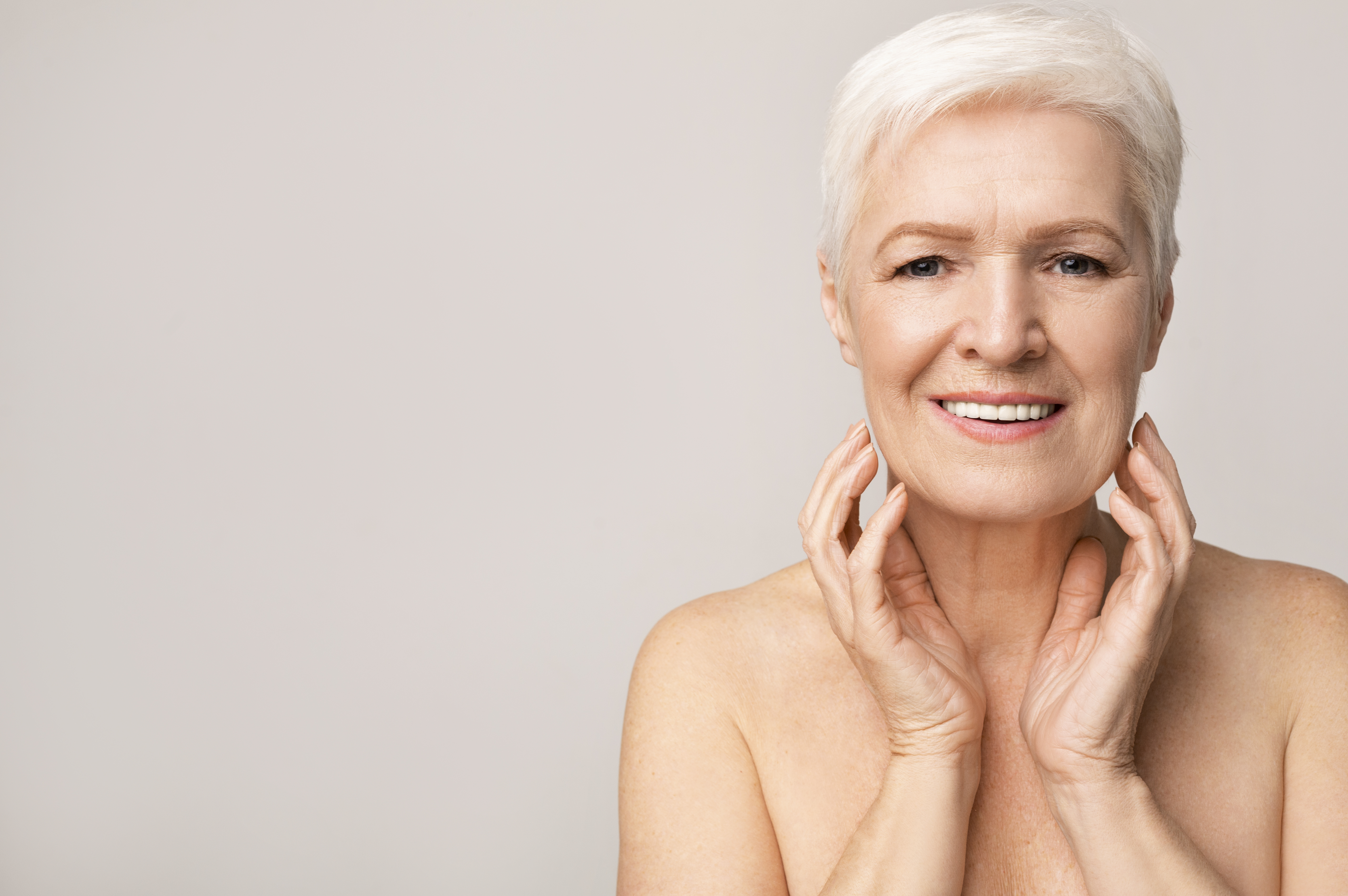 Portrait of attractive senior woman touching her chin and looking to camera over light studio background, free space